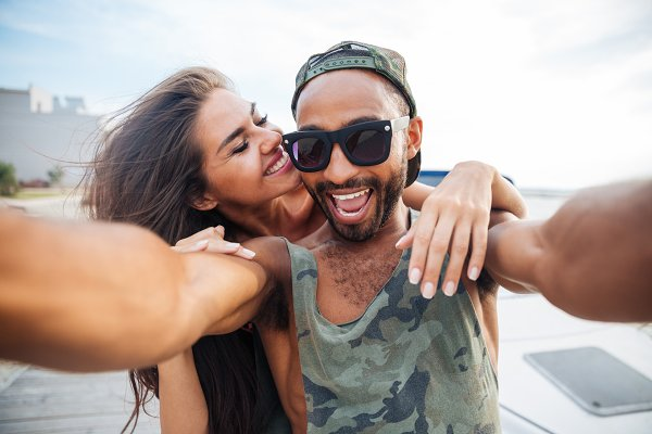 Smiling man and woman making selfie…