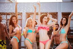 Group of best friends having fun dancing at swimming pool