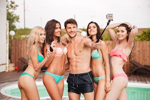 Happy man and group of women in swimsuits talking selfie