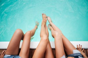 Legs of three young women in swimming pool