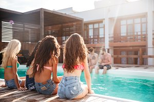 Back view of beautiful young women sitting near swimming pool