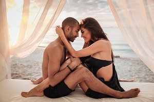 Couple sitting and hugging in bed on the beach
