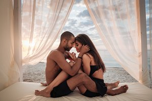 Passionate young couple sitting on the beach