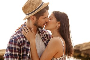Beautiful young couple standing and kissing on the beach