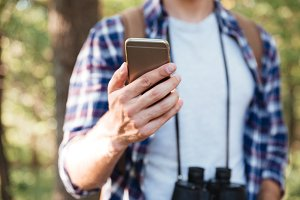 Cropped image of man with phone in forest