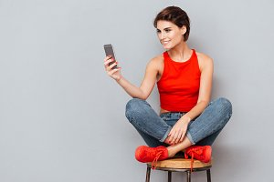 Smiling brunette woman sitting on the chair and using smartphone