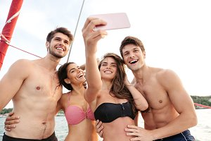 Smiling friends standing on yacht deck and making selfie