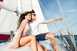Young beautiful married couple embracing on the yacht
