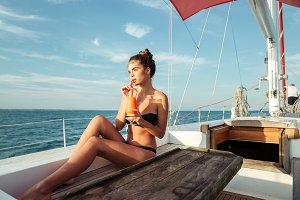 Young beautiful girl drinking cocktail while resting on a yacht