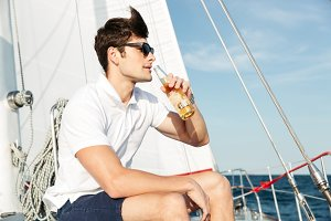 Handsome young man drinking beer while resting on the yacht
