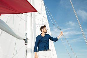 Young bearded man standing on a yacht