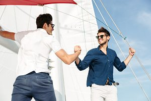 Two young handsome men greeting standing on the yacht