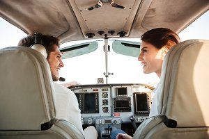 Couple looking at each other while sitting inside airplane cabin