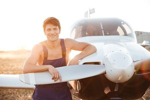 Mechanic in overall standing and looking at camera near airplane