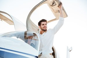 Cheerful man pilot getting out of the plane after landing