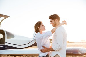 Happy couple in love standing near airplane
