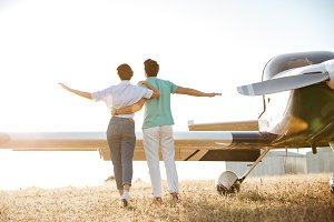 Back view of couple walking on field near small airplane