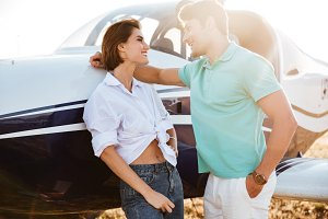 Couple talking and flirting near private airplane