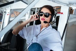 Attractive woman pilot in sunglasses and headset sitting in aircraft