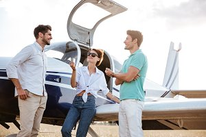 Happy friends standing and talking near small plane