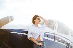 Woman in sunglasses standing outdoors near small private plane