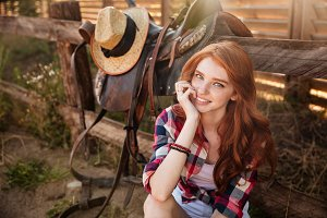 Close up portrait of a happy beautiful redhead cowgirl resting