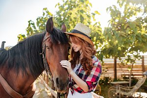Happy young woman cowgirl standing with her horse on ranch