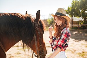 Cute lovely cowgirl taking care of her horse on ranch