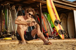 Young handsome surfer sitting and using smartphone outdoors