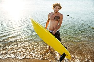 Young curly man with surf board standing in the ocean
