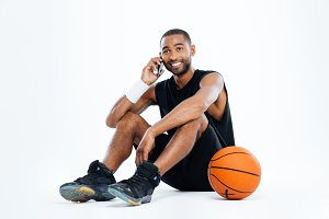 Happy man basketball player sitting and talking on cell phone