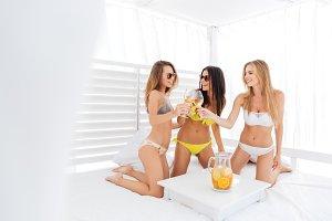 Three young happy beautiful girls in bikini drinking