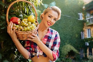 Cheerful lovely young woman holding basket of fresh fruits