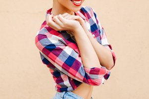Pretty cute pinup girl in plaid shirt standing and smiling