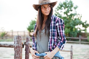 Beautiful young woman cowgirl in hat standing on ranch