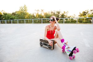 Roller girl in red swimsuit listening music with record player