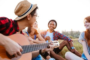Happy young people sitting outdoors and playing guitar together