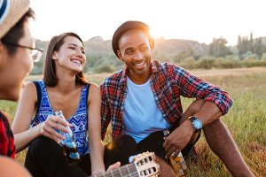 Cheerful couple drinking beer and soda with friends outdoors