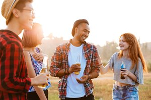 Group of happy young people laughing and drinking beer outdoors