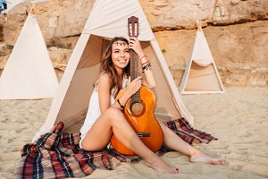 Smiling young hippie woman posing with guitar at the beach