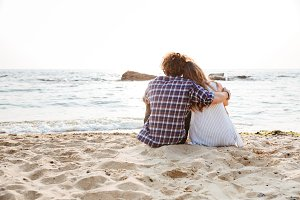 Back view of couple sitting and hugging on the beach