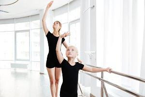 Little ballerina and teacher dancing tiptoes in dance studio