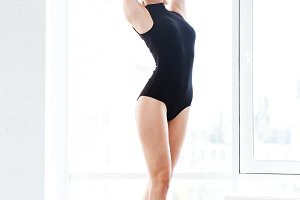 Woman ballerina in leotard dancing tiptoes in dance studio