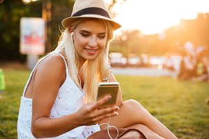 Smiling young woman listening to music from cell phone outdoors