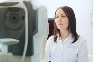 Ophthalmologist in eyes clinic doing diagnostic for patient - high technology in medicine