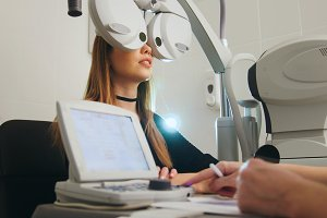 Blonde young female doing eye test with optometrist in medical center