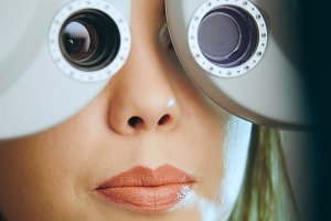 Ophthalmology concept - young woman checks the eyes on the modern equipment in the medical center