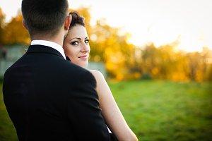 Brunette bride looks over groom