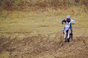 Crazy girl mx biker - motocross racer on dirt bike at sport track