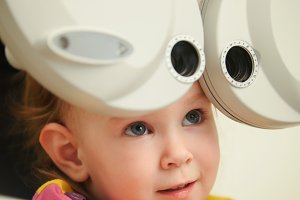 Modern healthcare - little cute girl in ophthalmologist room